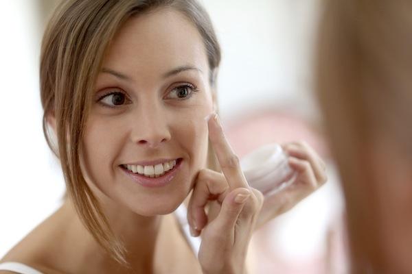 Portrait of woman in bathroom cleaning skin